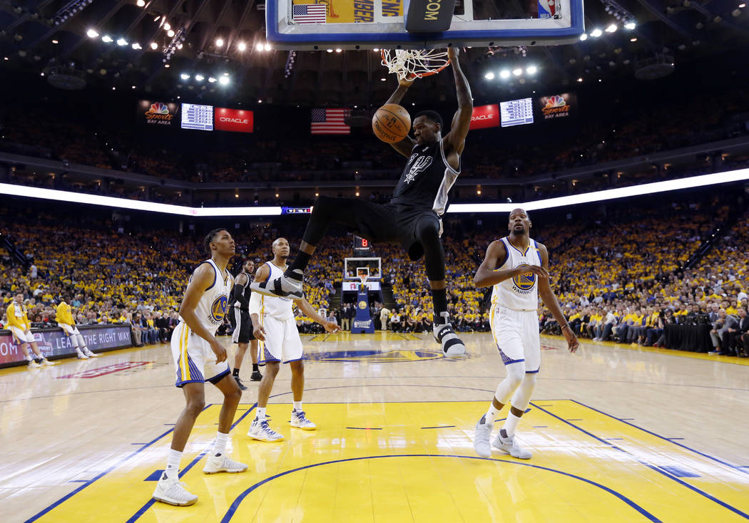 San Antonio Spurs' Dewayne Dedmon, center, dunks against the Golden State Warriors during the first half of Game 2 of the NBA basketball Western Conference finals, Tuesday, May 16, 2017, in Oaklan ...