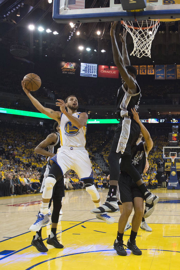 Golden State Warriors' Stephen Curry, left, shoots past San Antonio Spurs' Dewayne Dedmon during the first half of Game 2 of the NBA basketball Western Conference finals, Tuesday, May 16, 2017, in ...