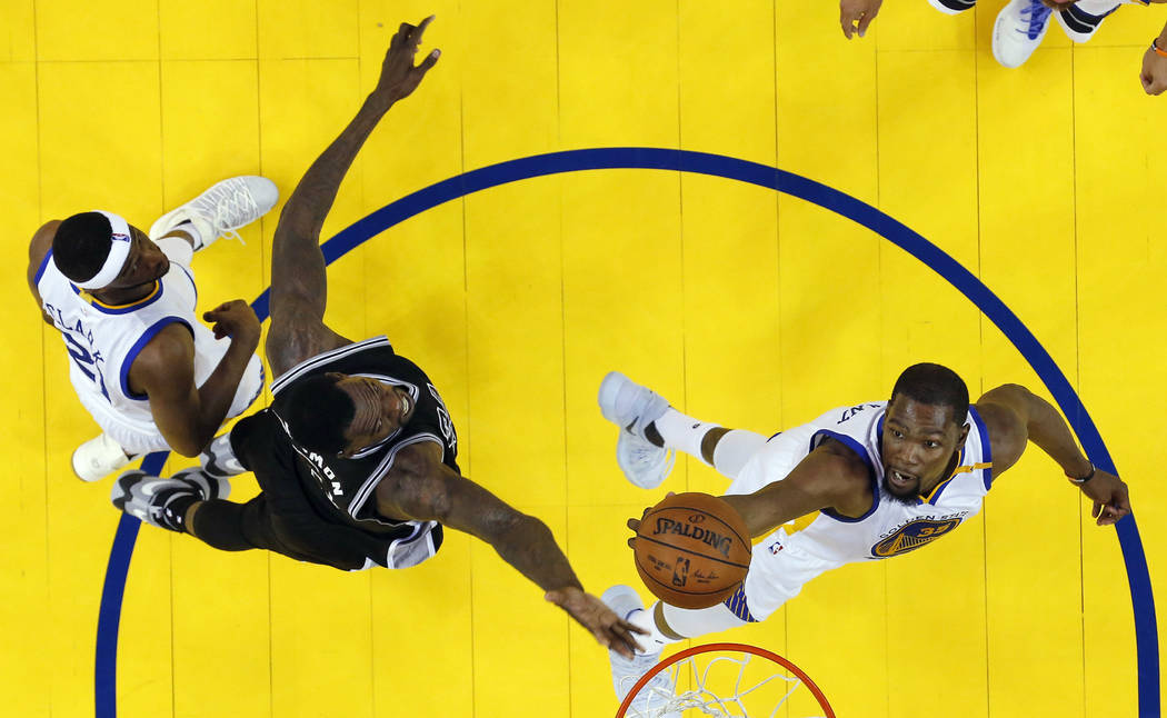 Golden State Warriors' Kevin Durant, right, works for a rebound against San Antonio Spurs' Dewayne Dedmon, center left, during the first half of Game 2 of the NBA basketball Western Conference fin ...