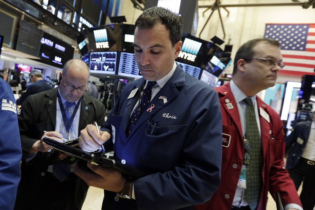 Trader Christopher LaGana, center, works on the floor of the New York Stock Exchange, Wednesday, May 17, 2017. Stocks are opening lower on Wall Street as banks and industrial companies fall. (Rich ...