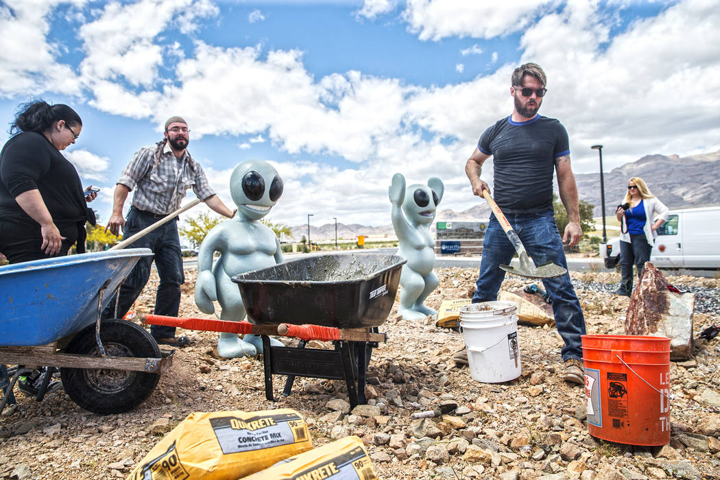 "Gia Ray, left, artist Jesse Smigel and James Norman work on the installation of Smigel's sculpture ""I Told You Not to Paint It Hot Orange"" on Thursday, May 18, 2017, in Las Vegas ..."