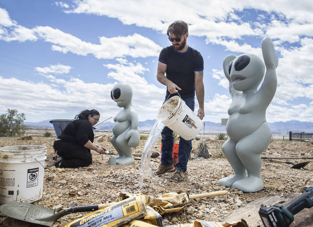 "James Norman, middle, and Gia Ray work on the installation of artist Jesse Smigel's sculpture ""I Told You Not to Paint It Hot Orange"" on Thursday, May 18, 2017, in Las Vegas. Ben ..."