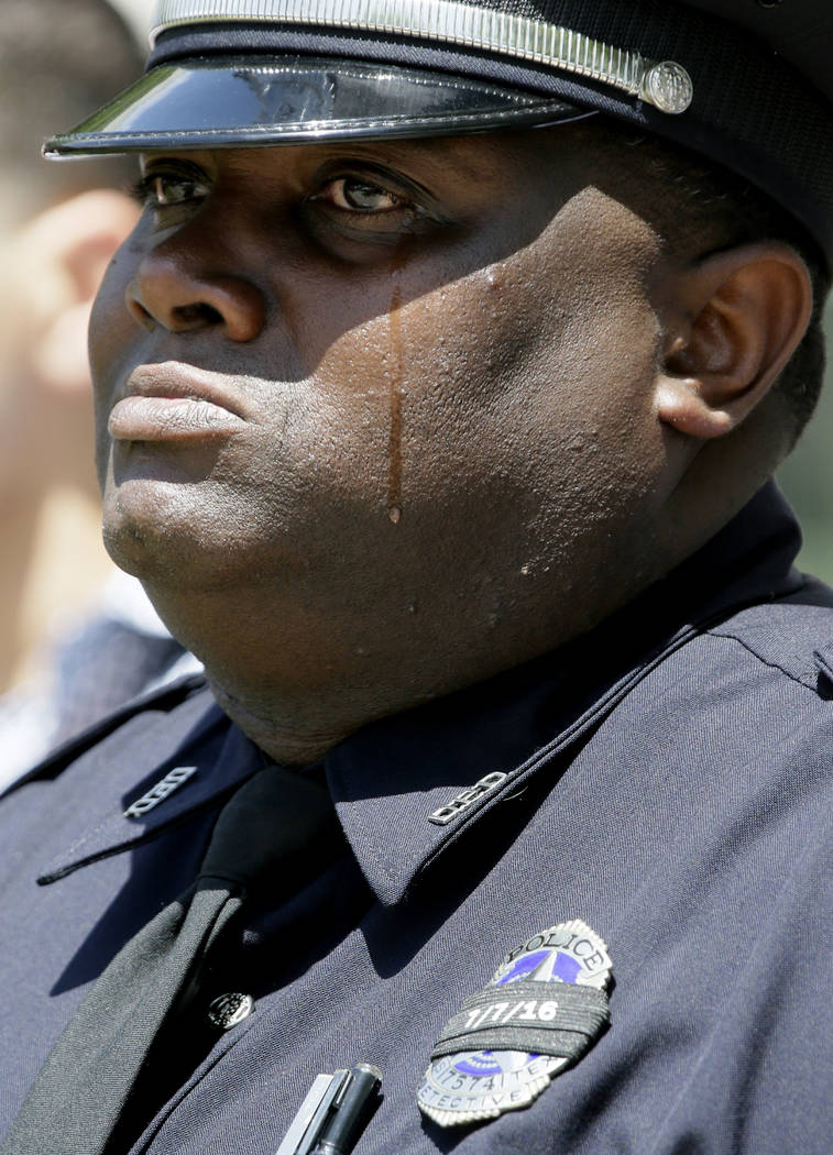 Dallas Police officer Demarcus Black sheds tears as the names of fallen peace officers are read during a memorial service in downtown Dallas, Wednesday, May 17, 2017. The Dallas Police Department  ...