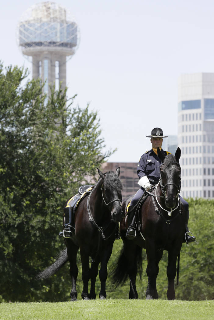 Dallas Police officer Ron Cunningham sits with a riderless horse during a memorial service for fallen peace officers in downtown Dallas, Wednesday, May 17, 2017. The Dallas Police Department and c ...