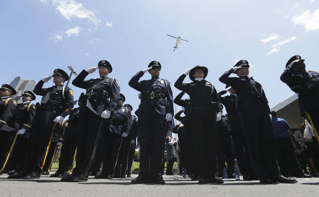 Peace officers from various agencies salute during a memorial service for fallen police in downtown Dallas, Wednesday, May 17, 2017. The Dallas Police Department and city leaders held a ceremony t ...