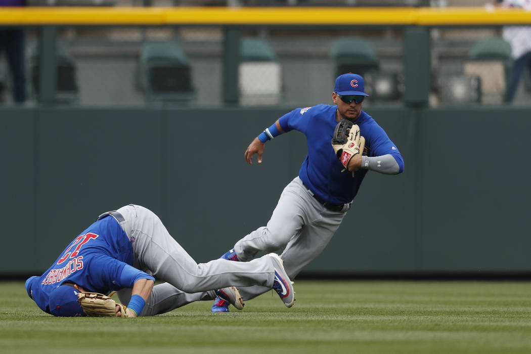 Chicago Cubs left fielder Kyle Schwarber, left, tumbles after missing a single off the bat of Colorado Rockies' Ryan Hanigan to drive in three runs as Cubs center fielder Albert Almora Jr. chases  ...