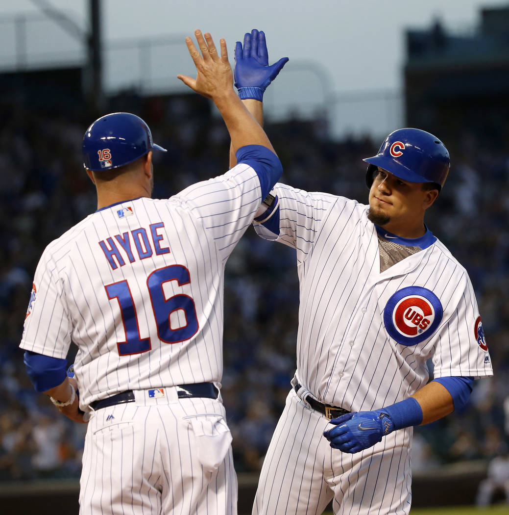 Chicago Cubs' Kyle Schwarber, right, celebrates his two-run single off Cincinnati Reds starting pitcher Scott Feldman with first base coach Brandon Hyde, during the second inning of a baseball gam ...
