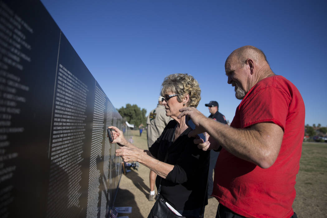 Lisa Mains, left, and her husband Robert take a photo of a friend's name on the replica Vietnam Veterans Memorial Wall hosted by the American Veterans Traveling Tribute at Craig Ranch Park on Frid ...