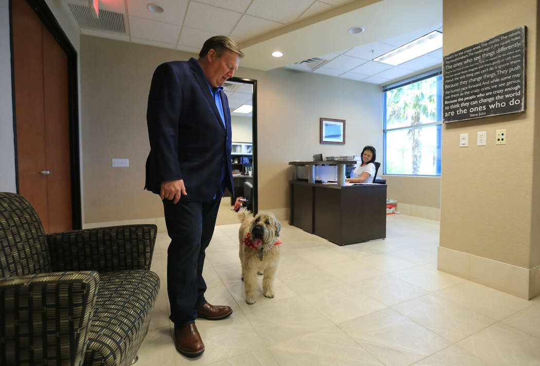 Sadie, a 9-year-old Wheaten Terrier, who has to approve all hires at Goettl Air Conditioning, stands with Ken Goodrich, 55, the CEO of Geottl Air Conditioning, in his office on Friday, May 19, 201 ...