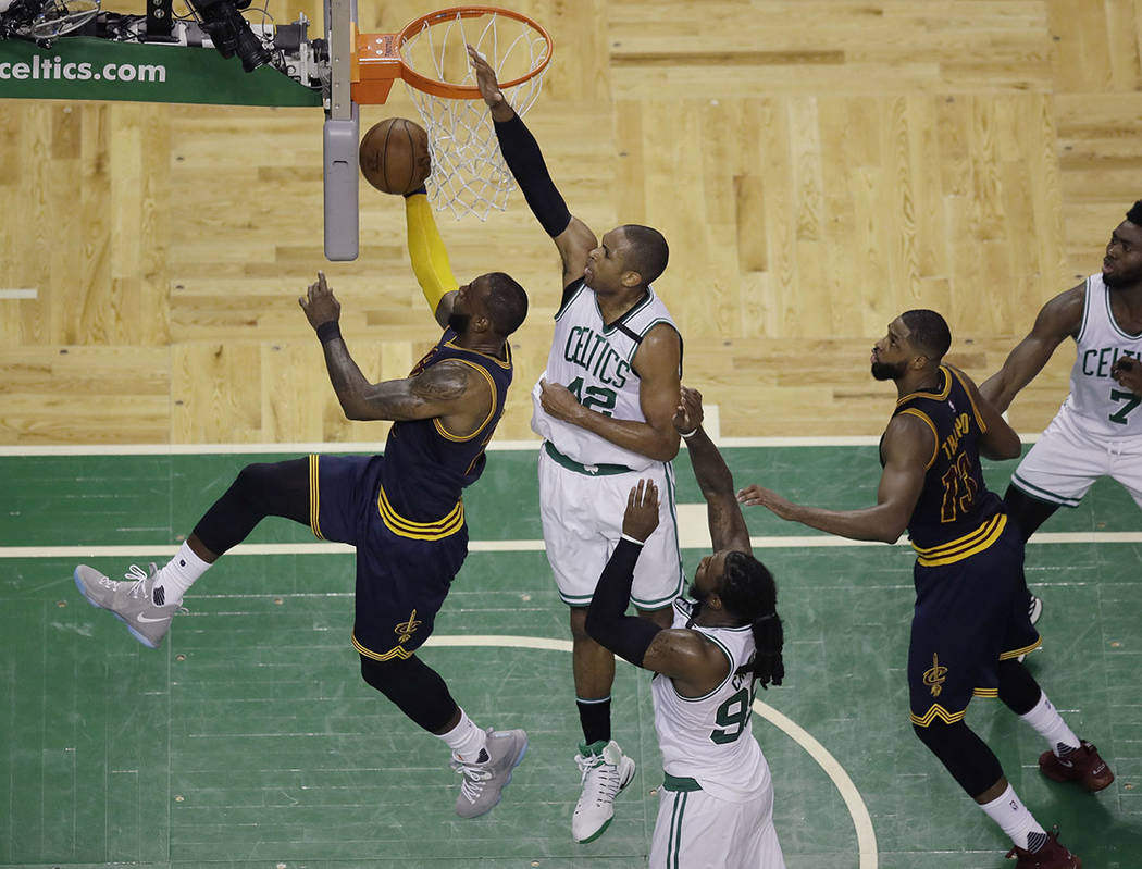 Cleveland Cavaliers forward LeBron James, left, drives for a layup in front of Boston Celtics center Al Horford (42) during the second quarter of Game 1 of the NBA basketball Eastern Conference fi ...