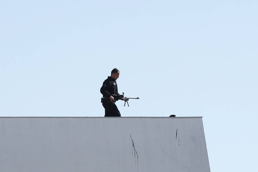 A policeman with a rifle gets into position prior to the opening ceremony and the screening of the film Ismael's Ghosts at the 70th international film festival, Cannes, southern France, Wednesday, ...