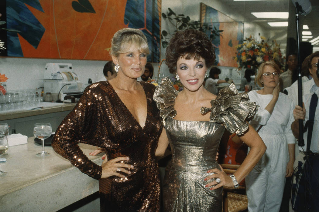 "Actress Joan Collins, right, poses with Linda Evans after modeling ""Dynasty"" fashions, Sept. 18, 1983. The CW will reboot the series this fall. (Doug Pizac/AP)"
