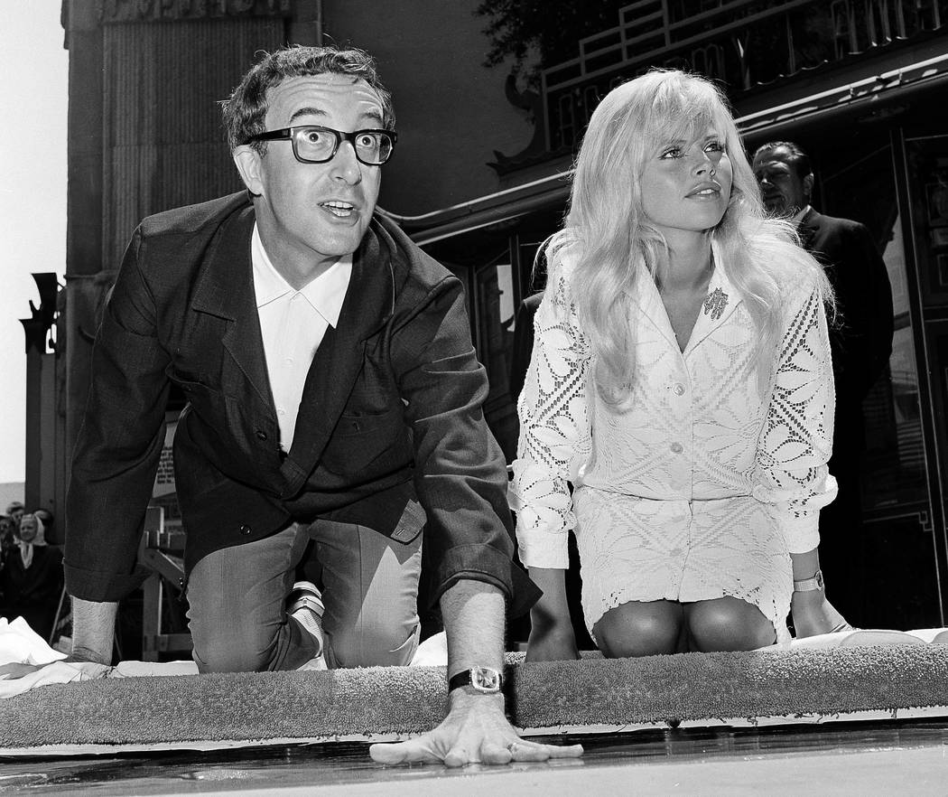 Comedian Peter Sellers, accompanied by his wife, actress Britt Eklund, puts his handprint in concrete at Grauman's Chinese Theater in Los Angeles on June 3, 1964.  (AP Photo, File)