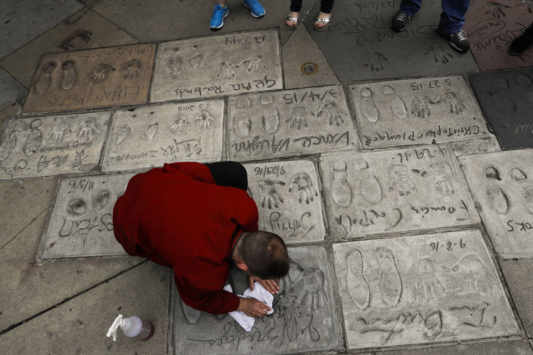 Door staff Chris Bayus cleans the hand and footprints of Hollywood stars in the forecourt of the TCL Chinese Theatre in Los Angeles on May 9, 2017. (Jae C. Hong/AP)