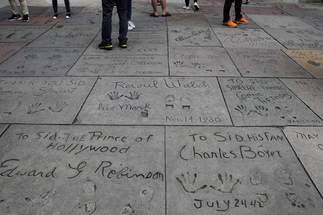 Tourists look at the hand and footprints of celebrities in the forecourt of the TCL Chinese Theatre in the Hollywood section of Los Angeles on May 9, 2017. (Jae C. Hong/AP)