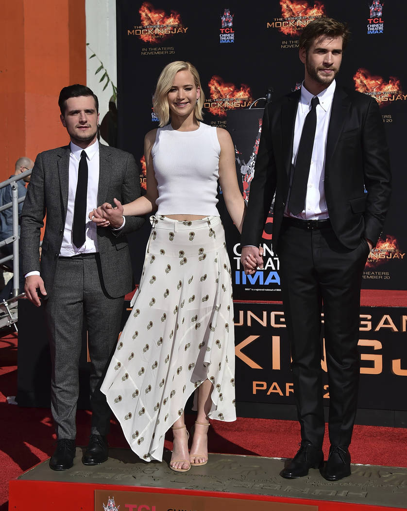 Josh Hutcherson, from left, Jennifer Lawrence and Liam Hemsworth place their feet in cement at a hand and footprint ceremony outside the TCL Chinese Theatre IMAX in Los Angeles on Oct. 31, 2015. ( ...