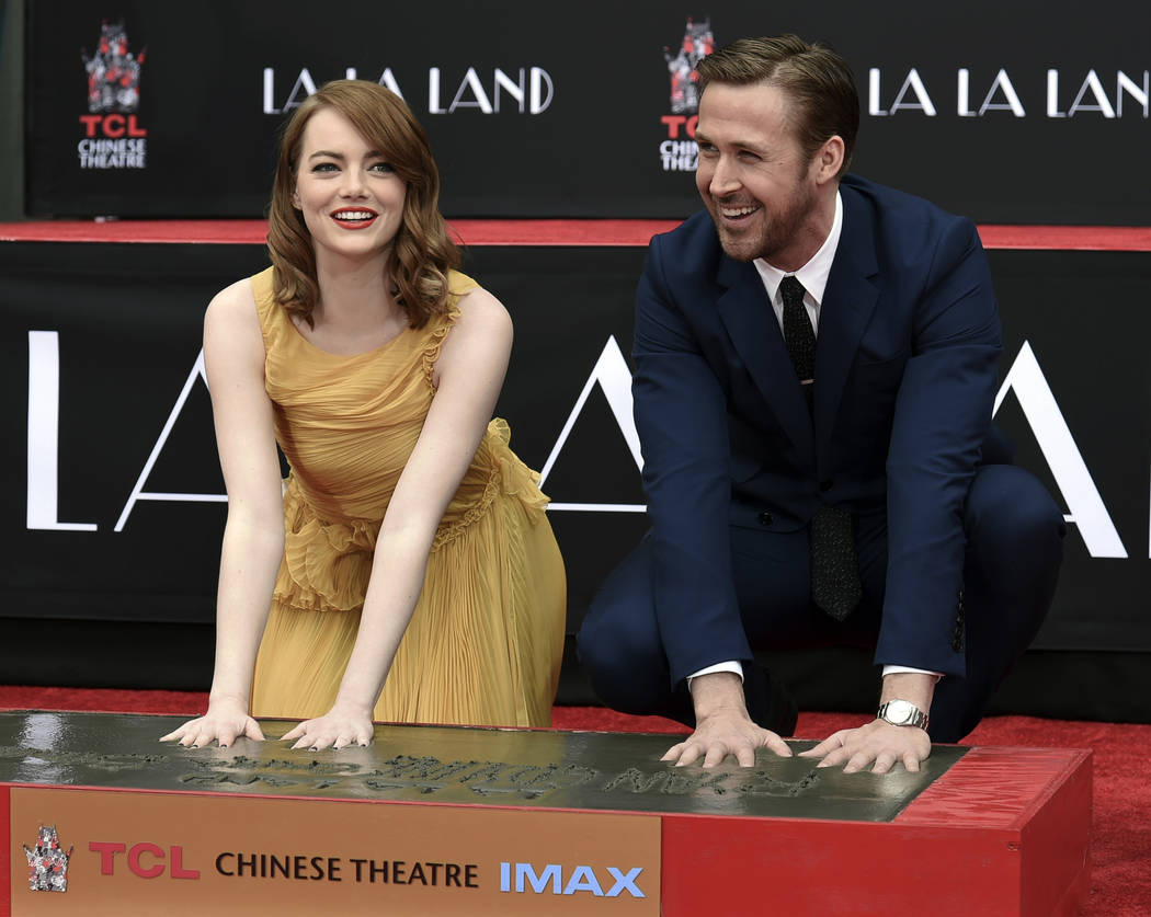 "Emma Stone, left, and Ryan Gosling, stars of the Oscar-nominated ""La La Land,"" place their hands in cement during a ceremony at TCL Chinese Theatre in Los Angeles on Dec. 7, 2016. (Richard Shotwel ..."