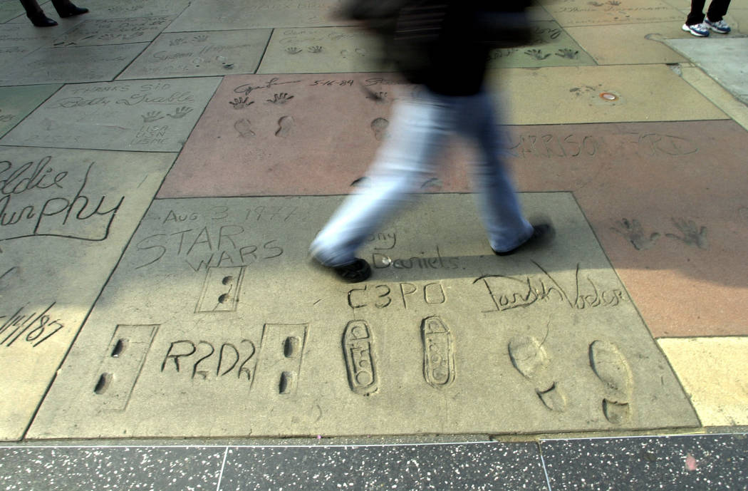 "A pedestrian walks over the signatures and foot prints of the original ""Star Wars"" characters R2-D2, C3PO and Darth Vader, that were set Aug. 3, 1977, in front of the Grauman's Chinese Theater in  ..."