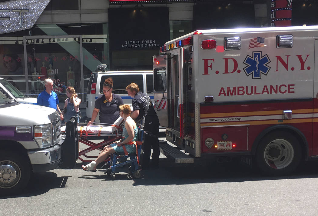 First responders assist one of the victims of a car crash, Thursday, May 18, 2017 in New York.  A man who appeared intoxicated drove his car the wrong way up a Times Square street and plowed into  ...