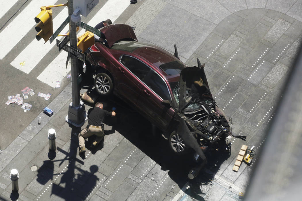 A police officer inspects a car crash, Thursday, May 18, 2017, in New York's Times Square.   A man who appeared intoxicated drove his car the wrong way up the Times Square street and plowed into p ...