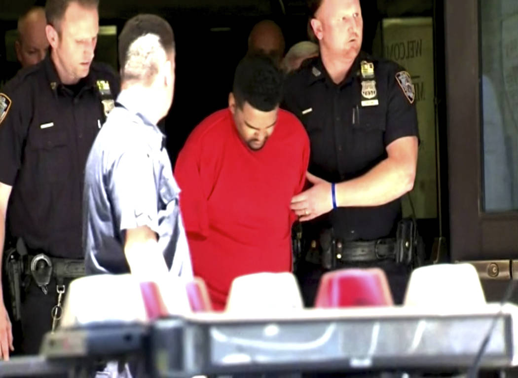 In this image taken from video provided by WABC Eyewitness News, New York City Police officers escort Richard Rojas from the Midtown South Precinct station house in New York, Thursday, May 18, 201 ...