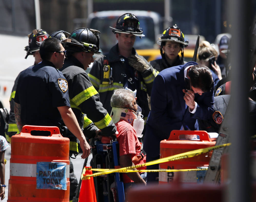 Emergency personnel treat a victim after a car ploughed through a crowd of pedestrians during lunchtime at New York's Times Square, Thursday, May 18, 2017. Police do not suspect a link to terroris ...