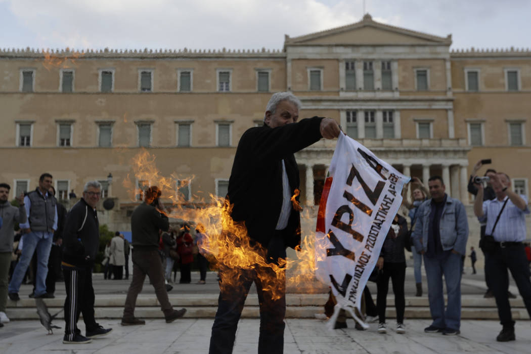 A protester burns a left-wing Syriza party flag outside the GreekParliament during a rally against new austeritymeasuresin Athens, Thursday, May 18, 2017.(Thanassis Stavrakis/AP)