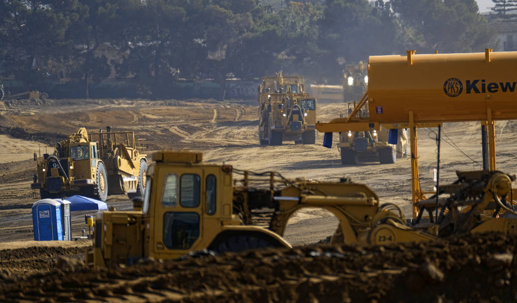 In this Nov. 17, 2016, file photo, earth movers clear an area where the new Los Angeles Rams stadium is being built in Inglewood, Calif. The opening date for the $2.6 billion football stadium unde ...