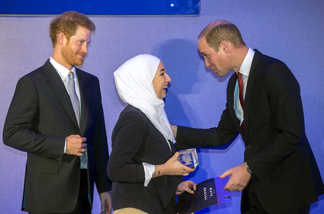 Britain's Prince William, right, gives an award to Elan Mon Gilford from Wales during a ceremony The Diana Award's inaugural Legacy Award, at St James' Palace in London, Thursday, May 18, 2017. (P ...