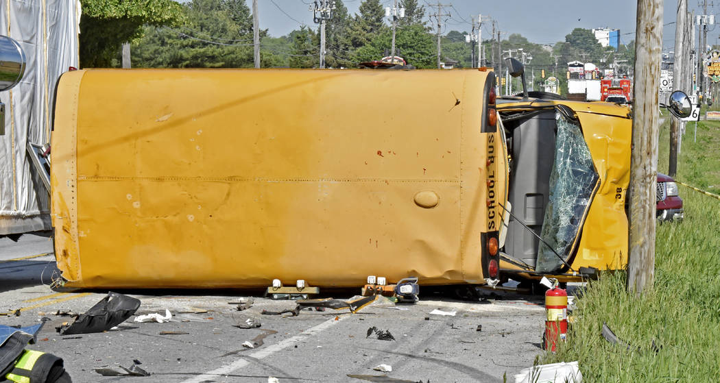 A damaged school bus lies on its side after a collision in East Lampeter Township, Pa., Wednesday, May 17, 2017. (Blaine Shahan/LNP via AP)