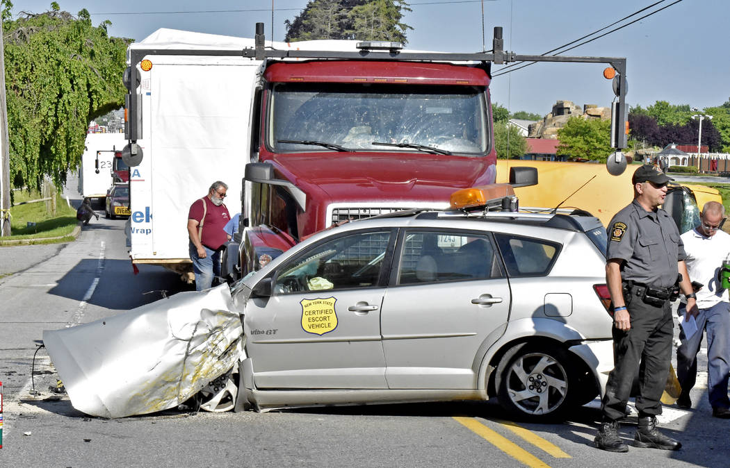 Emergency personnel work at the scene where an escort car, front, that was leading on oversized load, was struck by a passing vehicle that collided with a school bus in East Lampeter Township, Pa. ...
