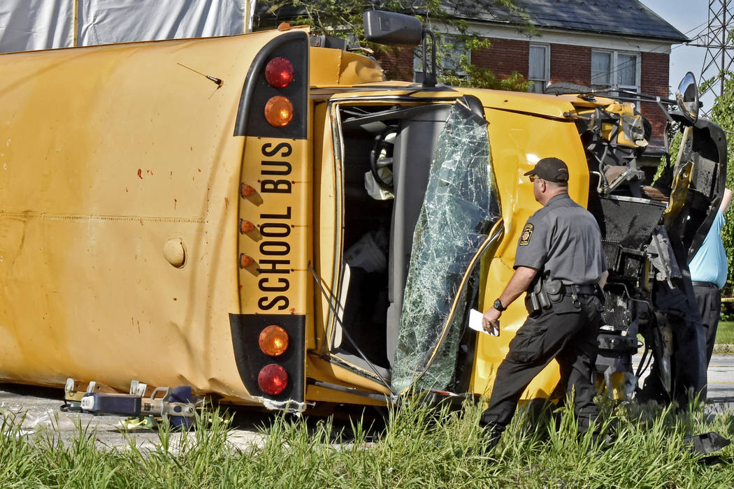 A Pennsylvania State Police trooper looks over a school bus that overturned after a collision in East Lampeter Township, Pa., Wednesday, May 17, 2017. (Blaine Shahan/LNP via AP)