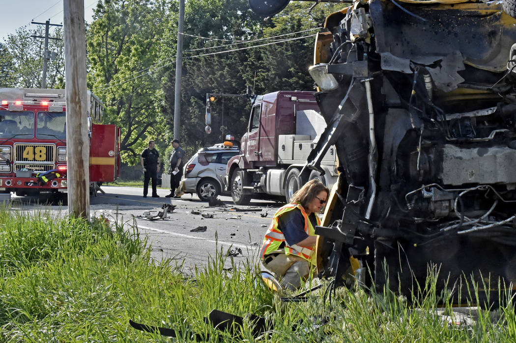 Emergency personnel look over a school bus that overturned after a collision in East Lampeter Township, Pa., Wednesday, May 17, 2017. (Blaine Shahan/LNP via AP)