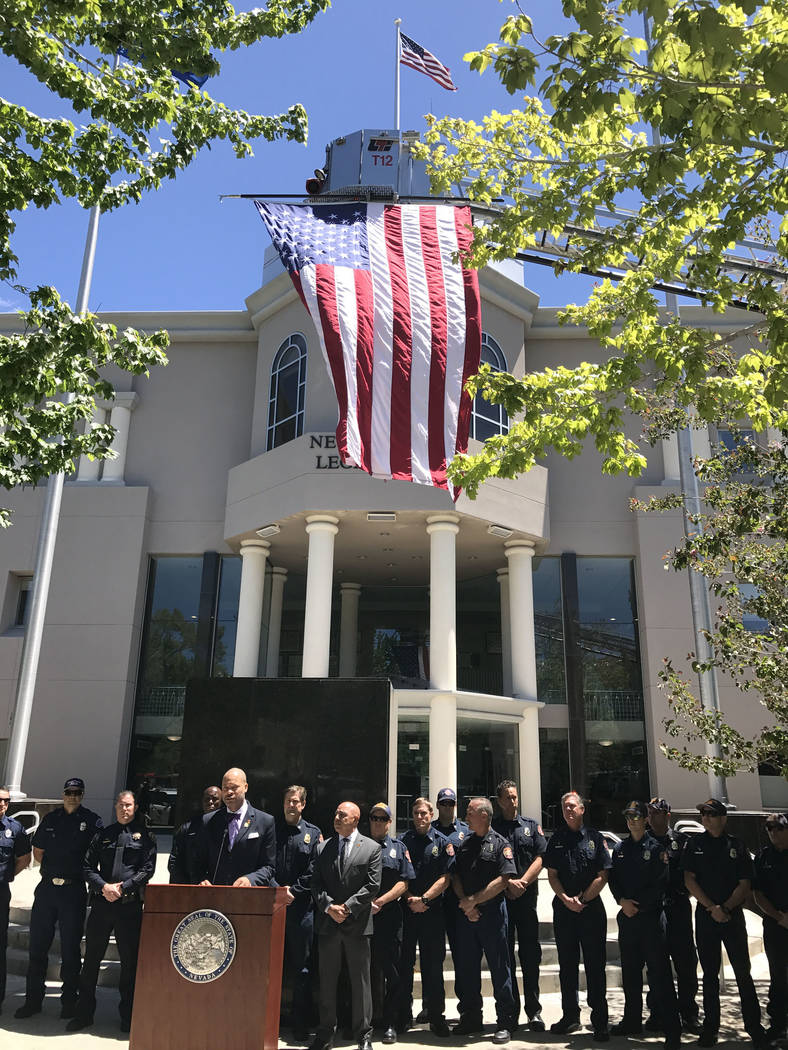 Senate Majority Leader Aaron Ford, D-Las Vegas, is flanked by law enforcement, firefighters and other emergency responders, Thursday, May 18, 2917, in Carson City. Ford announced two bills, one to ...