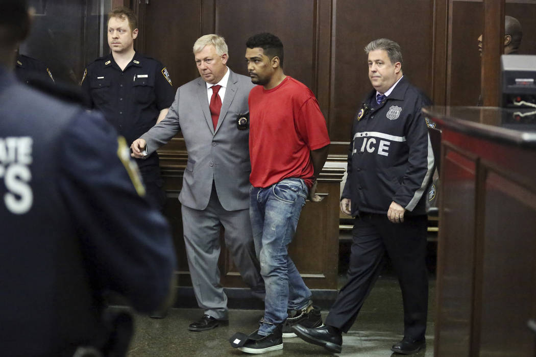 Richard Rojas, of the Bronx, N.Y., accused of mowing down a crowd of Times Square pedestrians, killing a teenage tourist, is escorted to his arraignment in Manhattan Criminal Court, in New York, F ...
