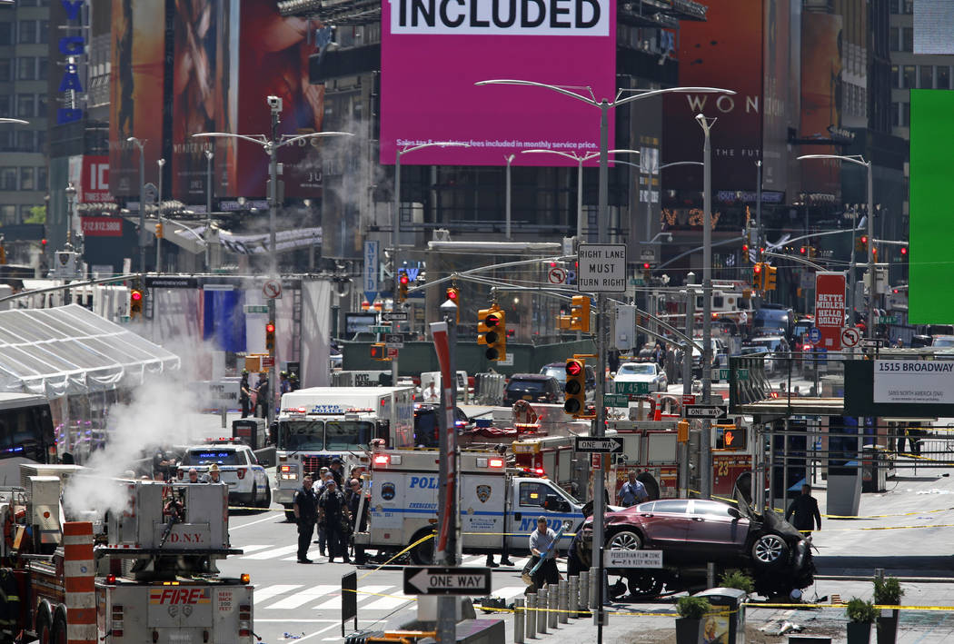 A smashed car, lower right, sits on the corner of Broadway and 45th Street in New York's Times Square after ploughing through a crowd of pedestrians at lunchtime on Thursday, May 18, 2017. (Seth W ...