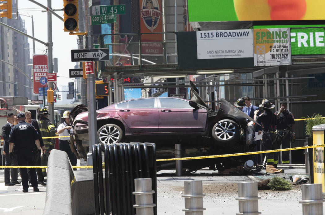 A car rests on a security barrier in New York's Times Square after driving through a crowd of pedestrians, killing one woman and injuring almost two dozen people, Thursday, May 18, 2017.  (Mary Al ...