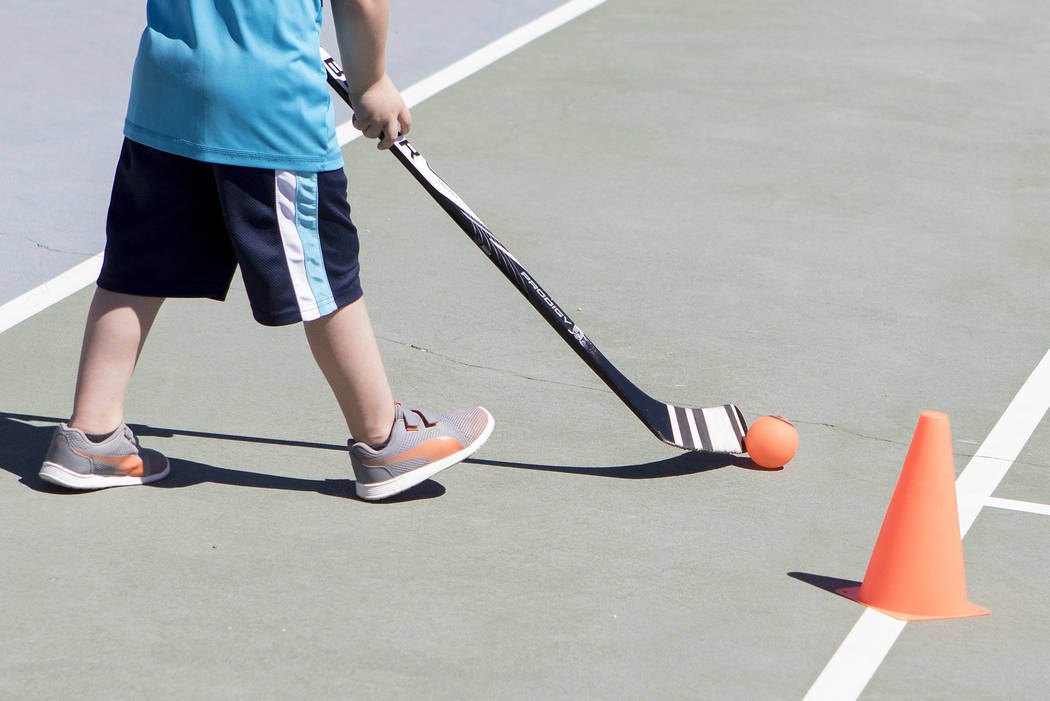 "A kid practices maneuvering the ball at ""Sticks For Kids,"" a street hockey clinic put on by the Vegas Golden Knights, at Paradise Park on Saturday, May 20, 2017 in Las Vegas. Bridget Bennett Las V ..."
