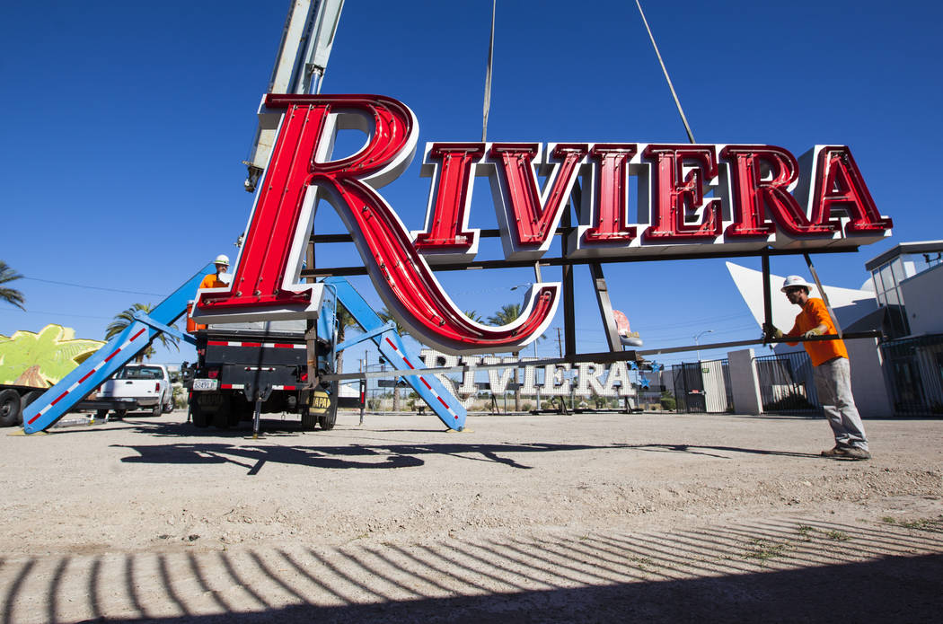 Charles Partridge of Federal Health, a visual communications company, right, helps place a Riviera hotel-casino sign at the Neon Museum in Las Vegas on Friday, May 19, 2017. The sign is one of app ...