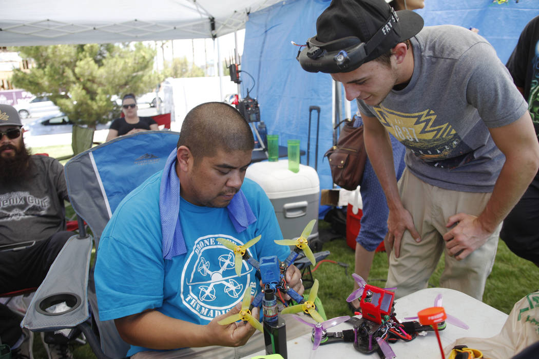 Addel Veloso, left, and Cooper Groves make adjustments to a drone at the King of Las Vegas drone tournament hosted by the Las Vegas Drone Club on Sunday, May 21, 2017, at Red Ridge Park in Las Veg ...