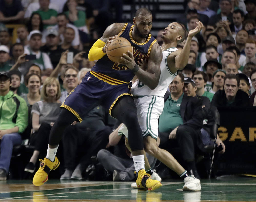 Cleveland Cavaliers forward LeBron James, left, muscles his way to the basket as Boston Celtics guard Avery Bradley, right, tries to defend during first half of Game 2 of the NBA basketball Easter ...