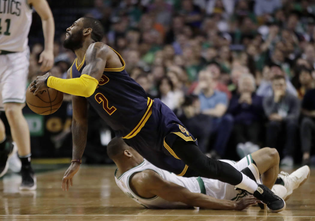 Cleveland Cavaliers guard Kyrie Irving (2) falls with Boston Celtics guard Avery Bradley (0) during the first half of Game 2 of the NBA basketball Eastern Conference finals, Friday, May 19, 2017,  ...