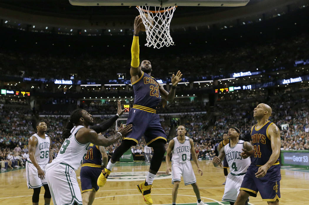 Cleveland Cavaliers forward LeBron James (23) drives between Boston Celtics forward Jae Crowder (99) and guard Isaiah Thomas (4) during first half of Game 2 of the NBA basketball Eastern Conferenc ...