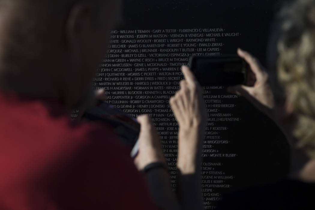 Robert Mains, left, and his wife Lisa take a photo of a friend's name on the replica Vietnam Veterans Memorial Wall hosted by the American Veterans Traveling Tribute at Craig Ranch Park on Friday, ...