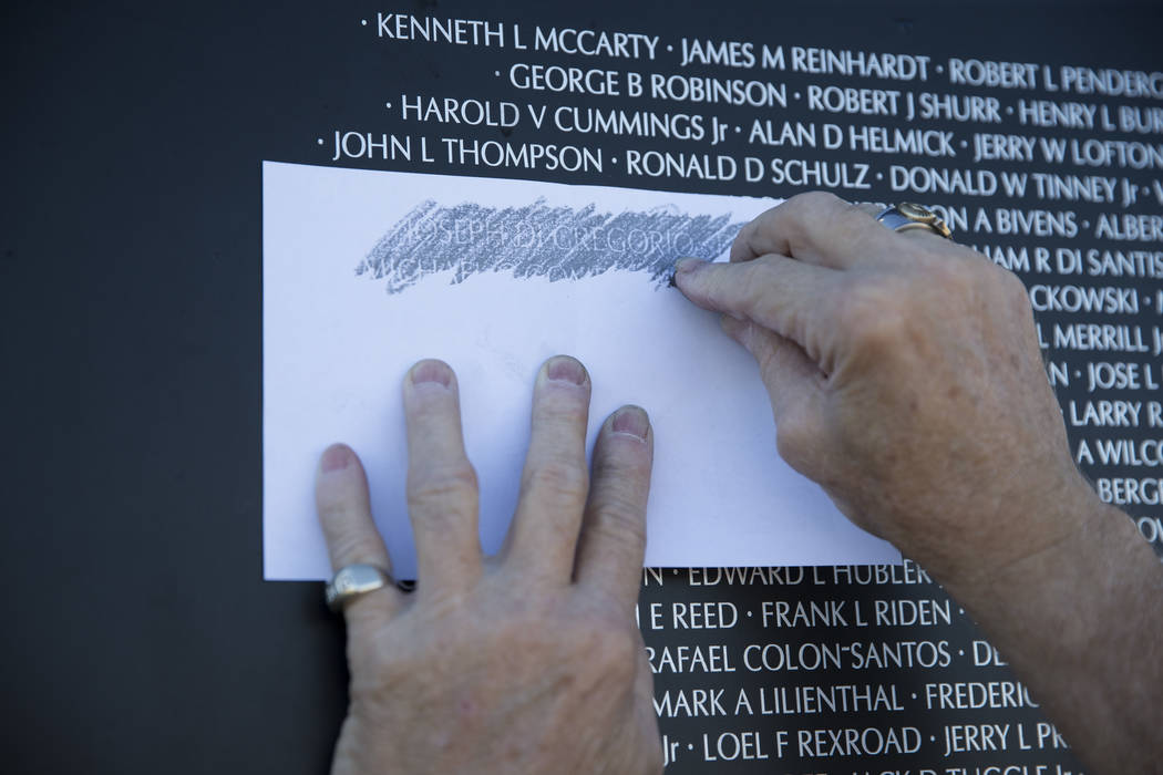 Vietnam veteran Keith Pence etches the name of a friend from the replica Vietnam Veterans Memorial Wall hosted by the American Veterans Traveling Tribute at Craig Ranch Park on Friday, May 19, 201 ...