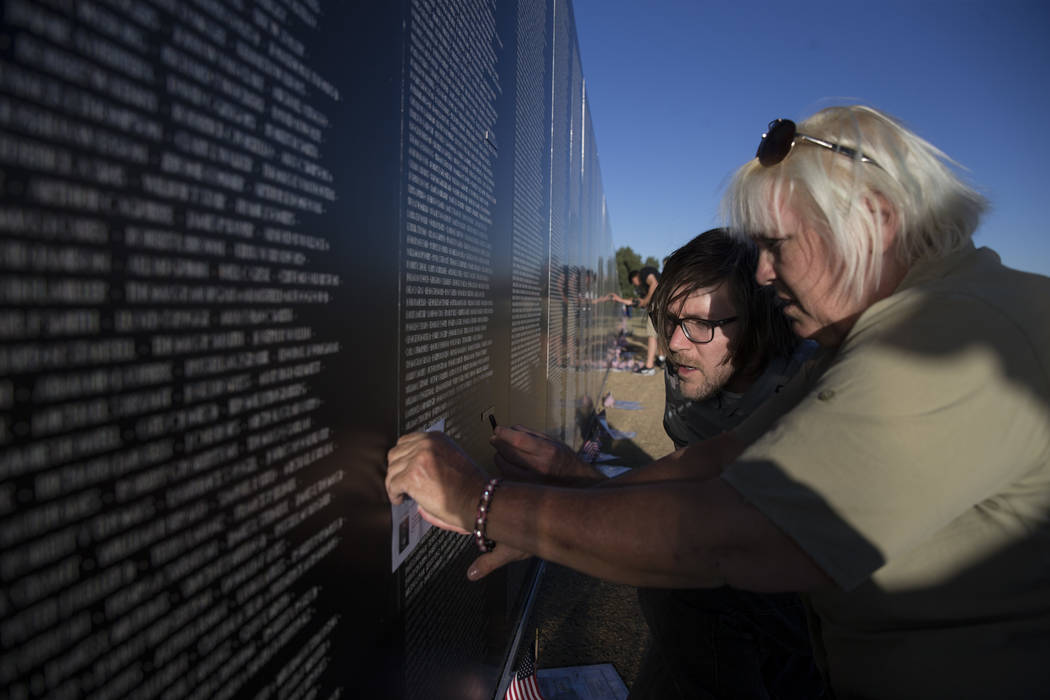 """U.S. Army veteran Gayle """"Stormy"""" Patrick with her son Jordan Meyers etch the name of her uncle on the replica Vietnam Veterans Memorial Wall during the opening ceremony hosted by ..."""