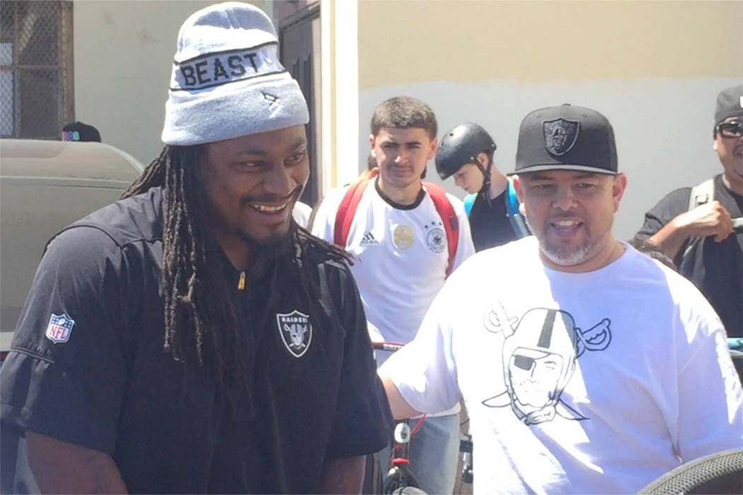The Raiders' Marshawn Lynch talks with friends during a bike ride in Oakland on Saturday. (Michael Gehlken/Las Vegas Review-Journal)
