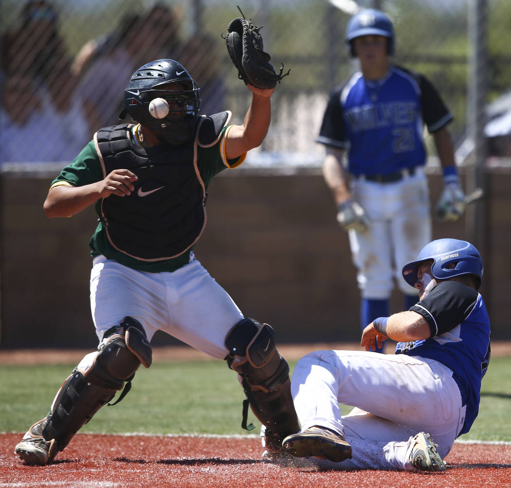 Basic's Trace Evans slides into home base to score a run as Rancho's Miguel Elicerio misses the ball during a Class 4A state baseball tournament game at Las Vegas High School in Las Vegas on Frida ...