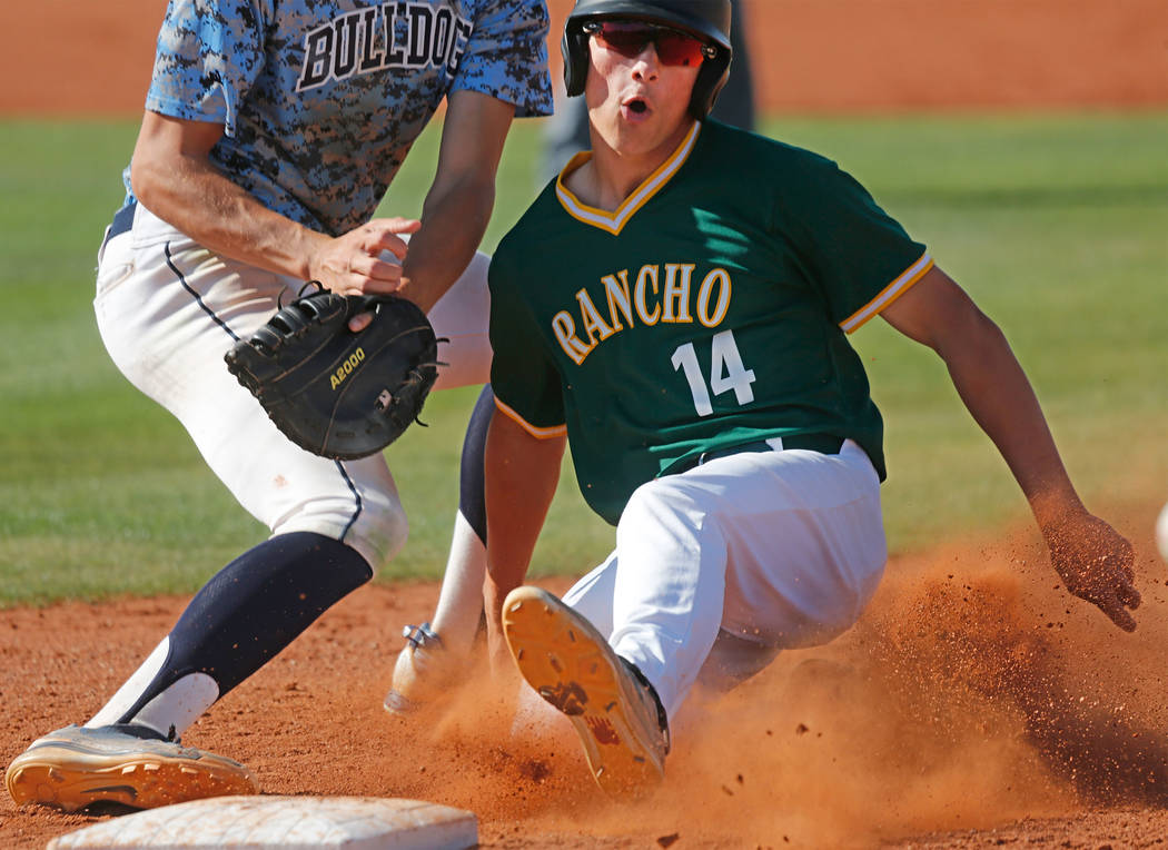Rancho's Joseph Walls (14) slides safely back to first base after attempting to steal second in the second inning of a state play-in baseball game at Las Vegas High School in Las Vegas, Monday, Ma ...