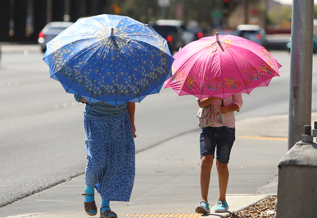 A woman and her granddaughter, who refused to give their names, hold umbrellas to protect themselves from sun as they walk along Rancho Road on June 2, 2016. Temperatures are expected to reach 100 ...